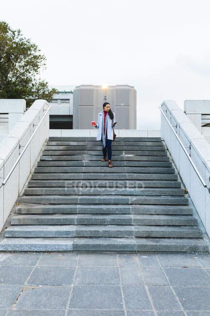 Азійська жінка тримає каву в сходах і користується смартфоном. Незалежна молода жінка у місті.. — стокове фото