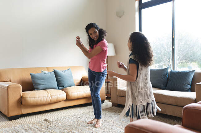 Щасливої змішаної раси мати й дочка танцюють у вітальні. Домашній спосіб життя і перебування вдома.. — стокове фото