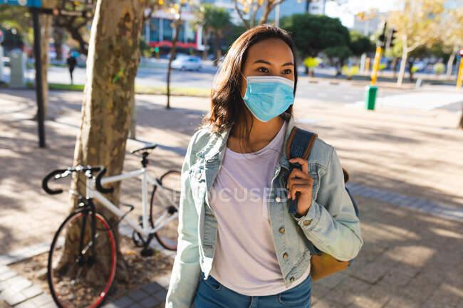 Mujer asiática con máscara facial caminando en el soleado parque. mujer joven independiente fuera y alrededor de la ciudad durante coronavirus covid 19 pandemia. - foto de stock