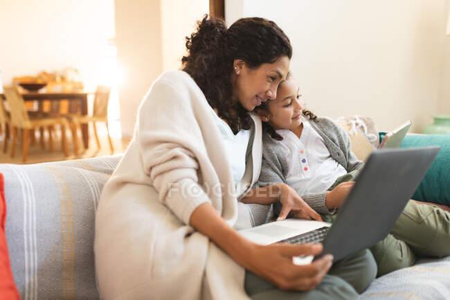 Sonriente madre de raza mixta e hija sentadas en el sofá, utilizando el portátil y la tableta. estilo de vida doméstico y pasar tiempo de calidad en casa. - foto de stock