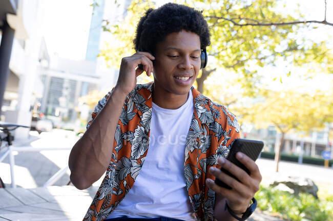 Uomo afroamericano in città seduto e utilizzando smartphone. nomade digitale in movimento, in giro per la città. — Foto stock