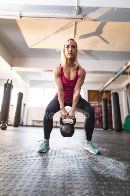 Сильная кавказка занимается спортом, поднимает тяжести. силовые и фитнес-кросс тренировки для бокса. — стоковое фото