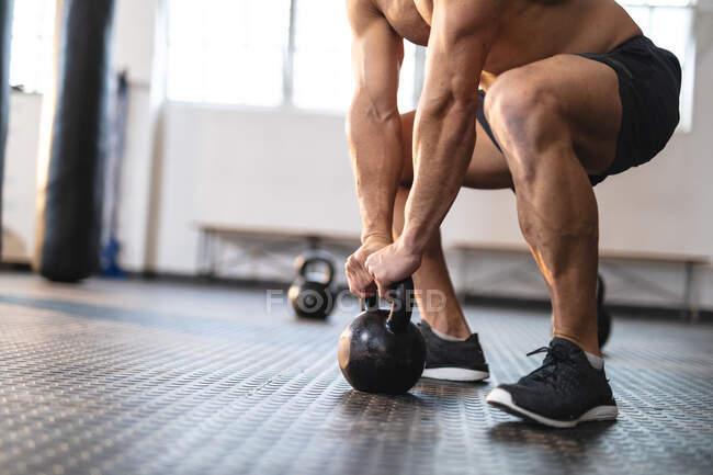 Сильний чоловік тренується в спортзалі, піднімаючи тягарі. міцність і пристосованість перехресна підготовка до боксу. — стокове фото