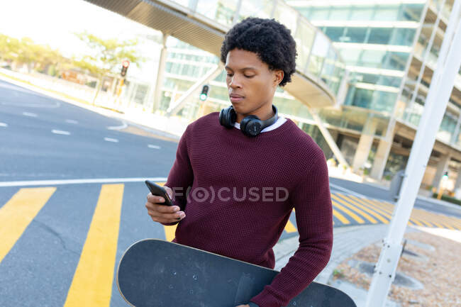 Uomo afroamericano in città utilizzando smartphone e tenendo skateboard. nomade digitale in movimento, in giro per la città. — Foto stock
