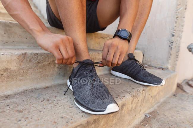 Fit homem exercitando-se na cidade amarrar sapatos. fitness e estilo de vida urbano ativo ao ar livre. — Fotografia de Stock