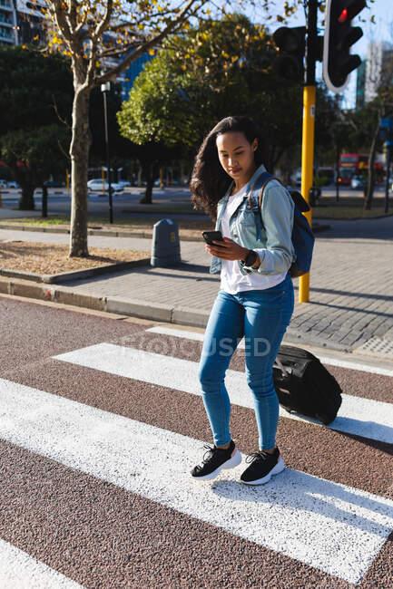 Азійська жінка перетинає дорогу з валізою і користується смартфоном. Незалежна молода жінка у місті.. — стокове фото