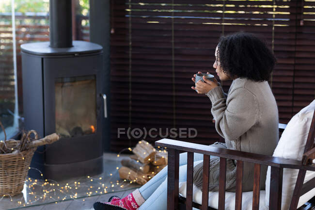 Feliz mujer de raza mixta en la sala de estar sentado junto a la chimenea sosteniendo taza y beber café. pasar tiempo libre en casa. . - foto de stock