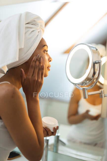 Mujer de raza mixta en baño aplicando crema facial para el cuidado de la piel, mirándose en espejo. estilo de vida doméstico, disfrutando del tiempo libre de autocuidado en casa. - foto de stock