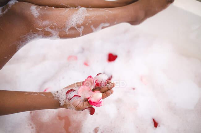 Primer plano de la mujer afroamericana teniendo baño de espuma mimar, añadiendo pétalos de rosa. estilo de vida doméstico, disfrutando del tiempo libre de autocuidado en casa. - foto de stock
