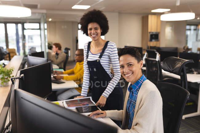 Retrato de diversas mujeres sonrientes creativas en el trabajo, sentadas en el escritorio, mirando a la cámara. trabajar en un negocio creativo en una oficina moderna. - foto de stock