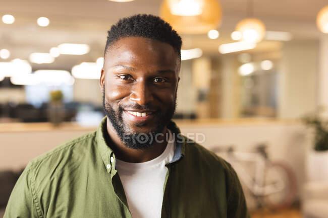 Retrato de sonriente afroamericano masculino creativo mirando a la cámara. trabajar en un negocio creativo en una oficina moderna. - foto de stock
