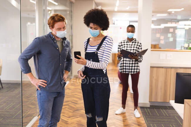 Diversos colegas masculinos y femeninos que usan máscaras faciales, trabajando juntos usando un teléfono inteligente. trabajar en negocios creativos en una oficina moderna durante la pandemia de coronavirus. - foto de stock
