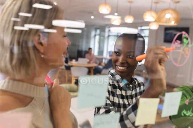 Diversas colegas sonrientes trabajando juntas, haciendo una lluvia de ideas, escribiendo notas. trabajar en un negocio creativo en una oficina moderna. - foto de stock