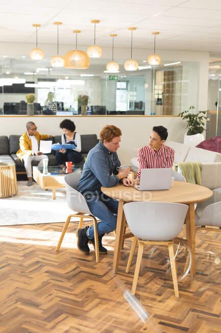 Diversos colegas masculinos y femeninos trabajando juntos en el área del salón del lugar de trabajo. trabajar en un negocio creativo en una oficina moderna. - foto de stock