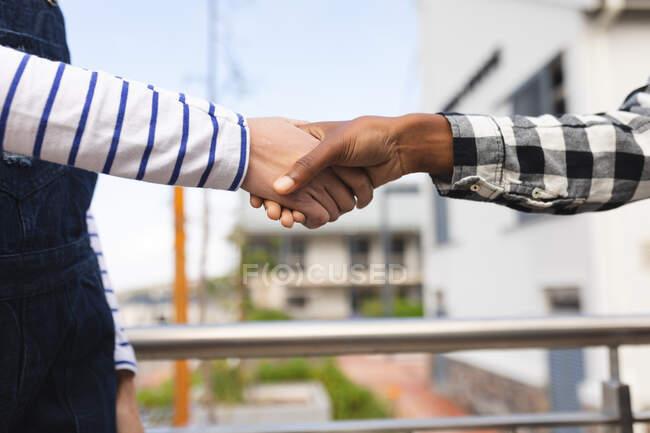 Diversos colegas masculinos y femeninos en el trabajo, estrechando las manos. trabajar en un negocio creativo en una oficina moderna. - foto de stock