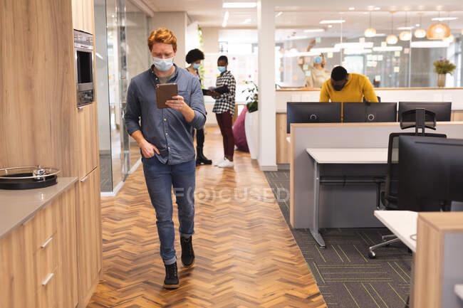 Diversos colegas masculinos y femeninos que usan máscaras faciales, trabajando juntos usando tableta. trabajar en negocios creativos en una oficina moderna durante la pandemia de coronavirus. - foto de stock