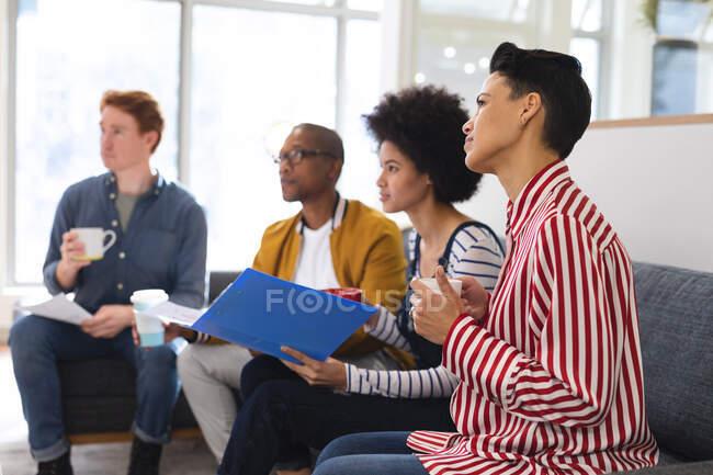 Diversos colegas masculinos y femeninos trabajando juntos, discutiendo en una reunión informal. trabajar en un negocio creativo en una oficina moderna. - foto de stock