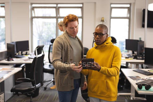 Diversos creativos masculinos en el trabajo, usando tableta, hablando. trabajar en un negocio creativo en una oficina moderna. - foto de stock
