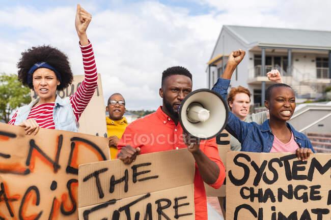 Hombre afroamericano usando megáfono y sosteniendo pancarta en una marcha de protesta. manifestantes por la igualdad de derechos y justicia en marcha. - foto de stock
