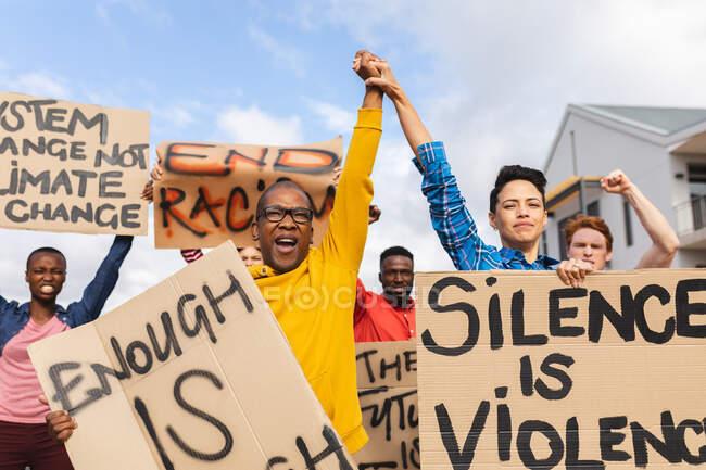 Multitud diversa de personas sosteniendo pancartas en la marcha de protesta. manifestantes por la igualdad de derechos y justicia en marcha. - foto de stock