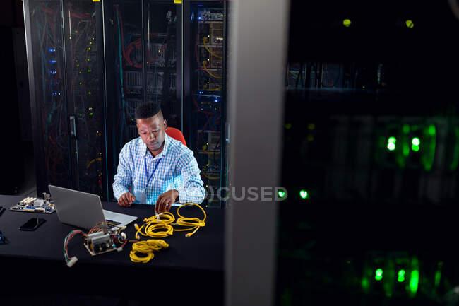 Homme technicien informatique afro-américain utilisant un ordinateur portable travaillant dans la salle des serveurs. stockage de l'information numérique et technologie des réseaux de communication. — Photo de stock