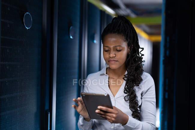 Technicienne en informatique afro-américaine utilisant une tablette travaillant dans la salle des serveurs. stockage de l'information numérique et technologie des réseaux de communication. — Photo de stock