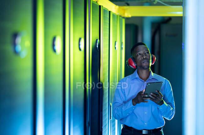 Un technicien informatique afro-américain portant un casque à l'aide d'une tablette travaillant dans la salle des serveurs. stockage de l'information numérique et technologie des réseaux de communication. — Photo de stock