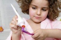Маленькая девочка прижимает зубную пасту к зубной щетке — стоковое фото