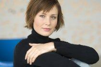 Portrait de femme aux cheveux courts assis et regardant la caméra — Photo de stock