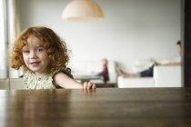 Портрет милой рыжей девочки, сидящей за столом — стоковое фото