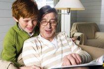 Senior man and boy reading book at home — Stock Photo