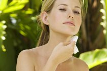 Portrait of young woman using cleansing cotton on neck outdoors — Stock Photo