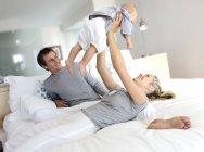 Parents gais et bébé s'amuser sur le lit dans la chambre, femme soulevant bébé — Photo de stock