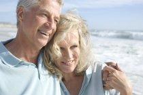 Портрет улыбающейся пары, обнимающейся на пляже — стоковое фото