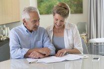 Старшая пара делает бумажную работу за столом дома — стоковое фото
