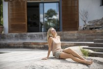Elegante donna bionda che si rilassa sulla pietra di fronte alla casa in estate — Foto stock