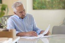 Сосредоточенный старший мужчина делает бумажную работу дома — стоковое фото