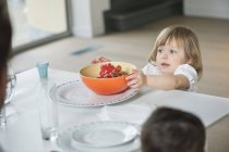 Little girl placing bowl on dining table — Stock Photo