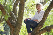 Contemplative teenage boy sitting on tree branch in summer — Stock Photo