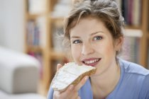 Porträt einer lächelnden Frau, die Toast mit Sahneaufstrich isst — Stockfoto