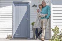 Portrait of romantic senior couple embracing outside of house — Stock Photo
