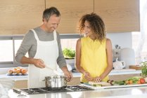 Happy couple preparing food in kitchen together — Stock Photo