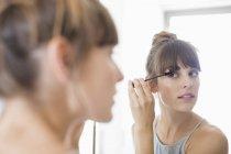 Сфокусированная молодая женщина наносит тушь перед зеркалом — стоковое фото