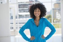 Porträt einer lächelnden Frau mit den Händen auf den Hüften — Stockfoto
