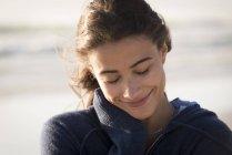 Крупный план молодой очаровательной женщины с закрытыми глазами, улыбающейся на пляже — стоковое фото