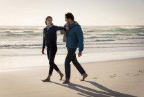Счастливая веселая молодая пара, гуляющая по пляжу осенью — стоковое фото