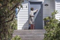 Donna con valigia bussare alla porta della casa di campagna — Foto stock