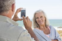 Man taking picture of wife with cell phone on beach — Stock Photo
