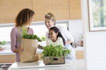 Старшая женщина с дочерью и внучкой смотрит на зелень на кухне — стоковое фото