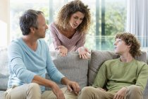 Happy family talking on sofa in living room at home — Stock Photo